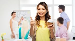 Asian woman drinking coffee and showing thumbs up. Architecture, education and business concept - happy young asian women drinking takeaway coffee from paper cup royalty free stock images