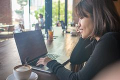 Asian woman drinking coffee and using laptop in coffee shop cafe stock photos