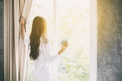 Asian women drinking coffee and wake up in her bed fully rested. Asian woman drinking coffee and wake up in her bed fully rested and open the curtains in the Stock Photography