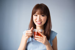 Asian woman drinking a cup of tea. Portrait of Asian woman drinking a cup of tea wearing blue dress  on blue background. Asian female model Royalty Free Stock Photography