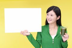 Smiling woman with a whiteboard. Asian woman drinking a glass of vegetable juice stock photo
