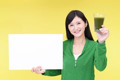 Smiling woman with a whiteboard. Asian woman drinking a glass of vegetable juice royalty free stock photography