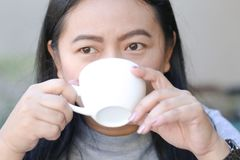 Asian women drinking hot coffee in a white cup stock images
