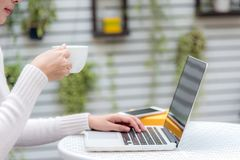 Asian women drinking hot coffee and working in the home garden.  Work space relaxing chill out work for office and design laptop s. Asian woman drinking hot Stock Photo