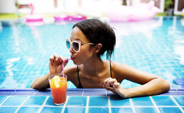 Asian woman drinking juice by the poolside Royalty Free Stock Photography