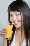 Asian woman drinking orange juice. Pretty asian woman drinking orange juice Royalty Free Stock Photo