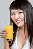 Asian woman drinking orange juice Stock Photography