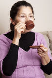 Asian woman drinking tea Royalty Free Stock Images