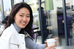 Asian woman drinking tea in the morning at restaurant with copy space.  Royalty Free Stock Photo