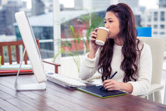 Asian woman drinking and using digital board while looking at computer monitor Stock Photography