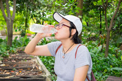 Asian woman drinking water in the park Royalty Free Stock Photo