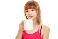 Asian woman drinking from white coffee cup Stock Photo