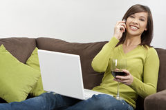 Asian Woman Drinking Wine on Phone Using Laptop Stock Image