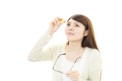 Asian woman dripping eye with eyes drops Royalty Free Stock Images