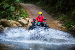 Asian woman driving an ATV through the river Spree. Stock Image