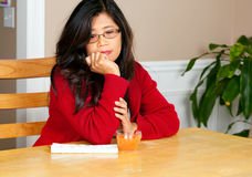 Asian woman in early forties sitting at table, depressed Royalty Free Stock Photography