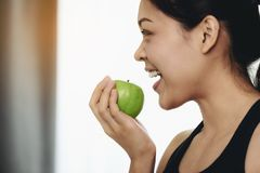 An asian woman is eating apple after exercising to take care of royalty free stock image