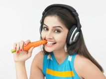 Asian woman eating a carrot Stock Images