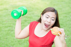 Asian woman eating hamburger with weight-lifting Royalty Free Stock Images