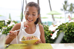 Asian woman eating hawaiian food tuna poke bowl. Asian woman eating a fresh raw tuna dish, hawaiian local food poke bowl, at outdoor restaurant table during Stock Photography