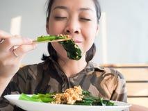 Asian woman eating kale. Royalty Free Stock Photo