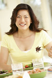 Asian woman eating meal at home Stock Images