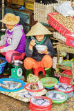 Asian woman eating and selling fresh fish in street market Stock Images