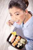 Asian woman eating sushi. Shallow depth of field, focu Royalty Free Stock Images
