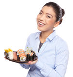 Asian woman eating sushi. Shallow depth of field, focu. Beautiful young woman eating sushi. Shallow depth of field, focus is on the eyes royalty free stock photo