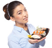 Asian woman eating sushi. Shallow depth of field, focu. Beautiful young woman eating sushi. Shallow depth of field, focus is on the eyes Royalty Free Stock Photo