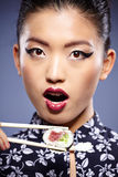 Asian woman eating sushi, Stock Photography