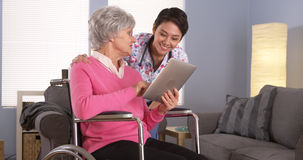 Asian woman and Elderly patient talking with tablet Stock Photography