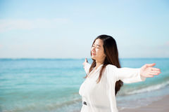 Asian woman enjoying beach, close eyes and open arms Royalty Free Stock Photography