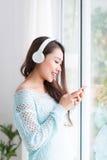 Asian woman enjoying and listening to music. Stock Photos