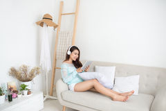 Asian woman enjoying sitting on couch and listening to music. Royalty Free Stock Photos
