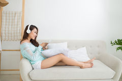 Asian woman enjoying sitting on couch and listening to music. Royalty Free Stock Image