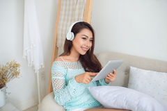 Asian woman enjoying sitting on couch and listening to music. Stock Photo