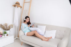 Asian woman enjoying sitting on couch and listening to music. Royalty Free Stock Images