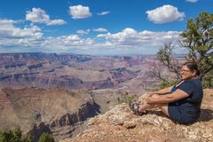 Woman sitting on the rim of the Grand Canyon Royalty Free Stock Images