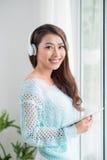 Asian woman enjoying view on windowsill and listening to music. Stock Photo
