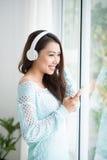 Asian woman enjoying view on windowsill and listening to music. Stock Image