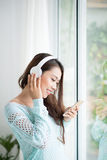 Asian woman enjoying view on windowsill and listening to music. Stock Image