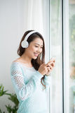Asian woman enjoying view on windowsill and listening to music. Stock Photo