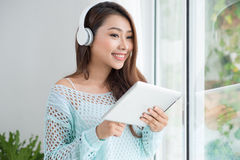 Asian woman enjoying view on windowsill and listening to music. Royalty Free Stock Images