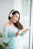 Asian woman enjoying view on windowsill and listening to music. Stock Photography