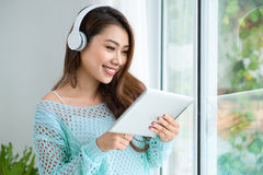 Asian woman enjoying view on windowsill and listening to music. Royalty Free Stock Image