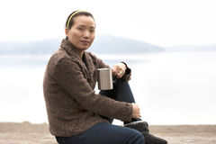 Asian woman enjoys coffee by lake. Stock Photography