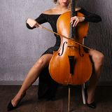 Asian woman in an evening dress playing the cello royalty free stock photos