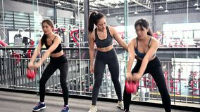 Asian woman exercise and lifestyle at fitness gym. Sporty woman workout with trainer and dumbbell weight. Wellness and healthy