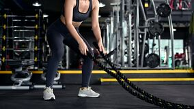 Asian woman exercise and solo lifestyle at fitness gym. Sporty woman workout alone with Battle rope. Wellness and healthy